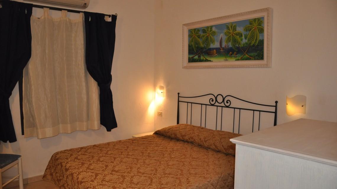 Residence San Teodoro 1. Camera da letto appartamento bilocale